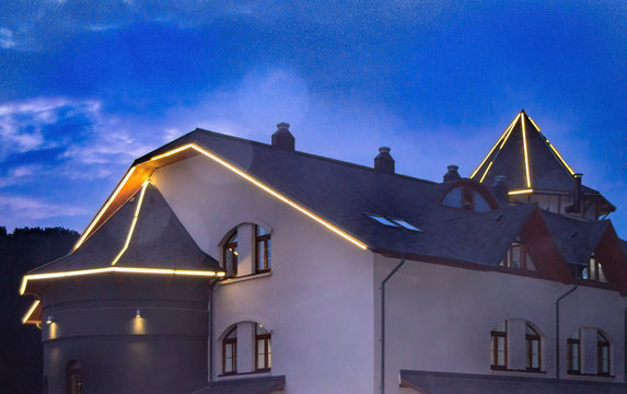 Luxury stylish mansion with a roof illuminated by led strips against a dark sky, a view of a modern house decorated for Christmas, at night