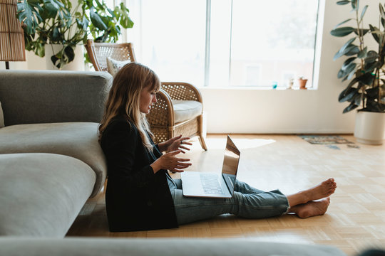 Woman working from home using a laptop screen mockup