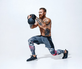 Sporty man doing lunges with kettlebell. Photo of man with naked torso on white background. Strength and motivation