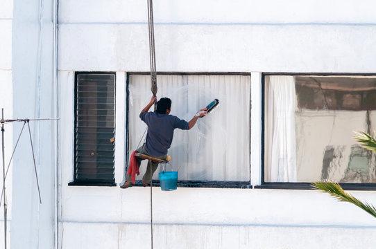Trabajador limpia ventana exterior en edificio de Ciudad de México con pocas medidas de seguridad