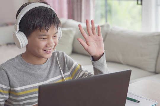 Preteen tween teen Asian boy making facetime video calling with laptop at home, using zoom  online virtual class , social distancing ,homeschooling,learning remotely during covid coronavirus pandemic