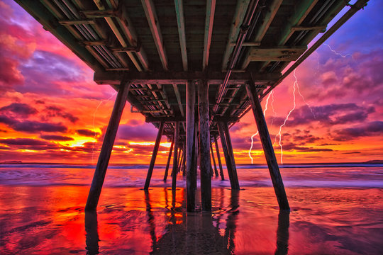 sunset over the sea, the power of nature over a wooden pier