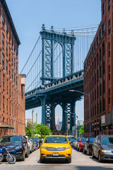 New York, USA - May 26, 2018: Yellow cab on a street in Dumbo of New York City. It is a major attraction in New York with view of Manhattan Bridge.