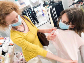 Mother and daughter in shopping mall with protective medical masks for protection of virus in time...