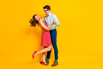 Full size photo of two people girl guy dance ballroom hold hand enjoy wear suspenders stilettos dotted blue shirt green socks pants isolated over bright shine color background