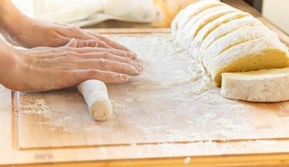 Wyrabianie domowego ciasta. Dłonie ugniatające ciasto na kluski. Gotowanie w domu.