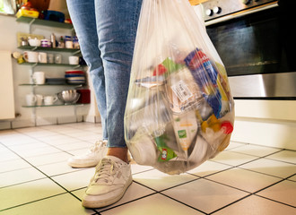 Woman standing in a kitchen carrying a bag with plastic waste