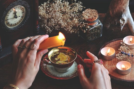 Wiccan witch wearing vintage jewelry holding yellow candle and pouring wax into a red gold vintage teacup as a divination. Reading Candle Wax - Carromancy, Ceroscopy among nature items dried flowers