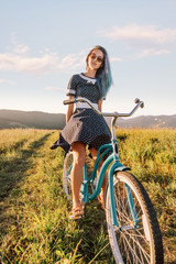 Woman sitting on a bicycle cruiser on countryside path in summer.