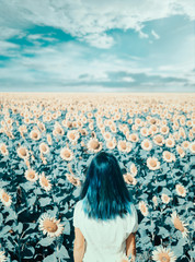Back view of woman standing in sunflowers field, cyan color effect.