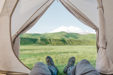 Hiker man lying in a tent and enjoying view of mountain Elbrus, pov.