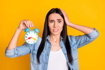 Close-up portrait of her she nice attractive lovely pretty charming discontent confused girl worrying holding in hand clock missed call isolated on bright vivid shine vibrant yellow color background