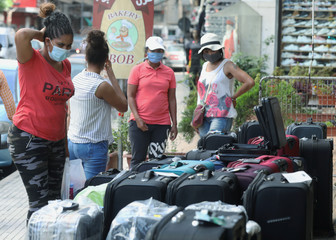 Women wearing face masks look at luggages displayed for sale in Dora