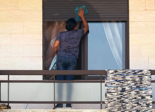 A foreign domestic worker cleans a window blinds in Beirut