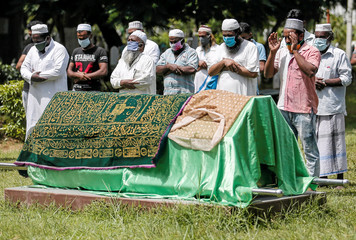 Men pray in front of the coffin of a woman who died in a stampede in Colombo