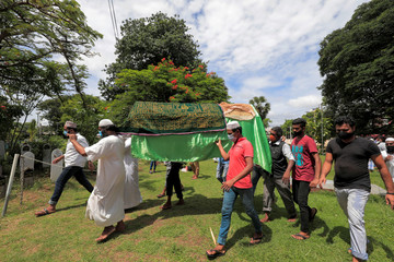 Men carry the coffin of a woman who died in a stampede in Colombo