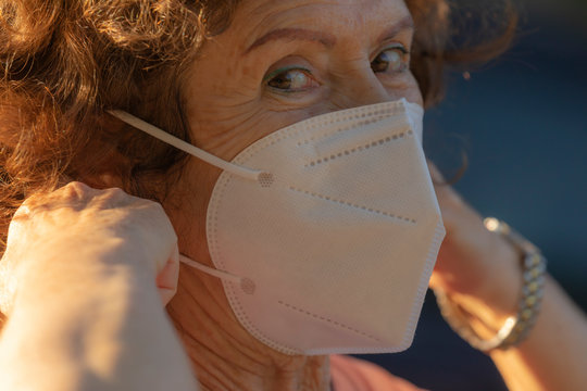 A real woman teaches how to put on the protective mask to prevent the spread of the COVID-19 virus to other people while walking down the street in the Retiro district of Madrid, Spain.