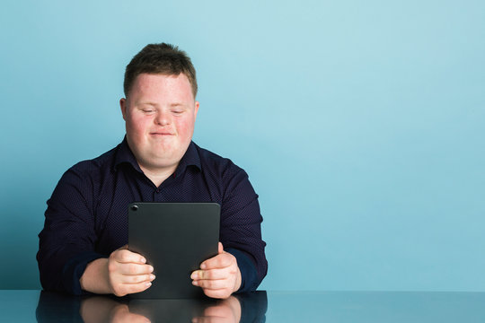 Cute boy with down syndrome homeschooling using a digital tablet during the coronavirus pandemic