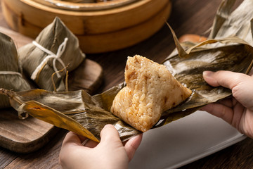 Dragon Boat Festival food - Rice dumpling zongzi, young Asian woman eating Chinese traditional food...