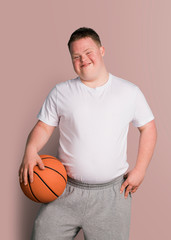 Cute athletic boy with down syndrome holding a basketball