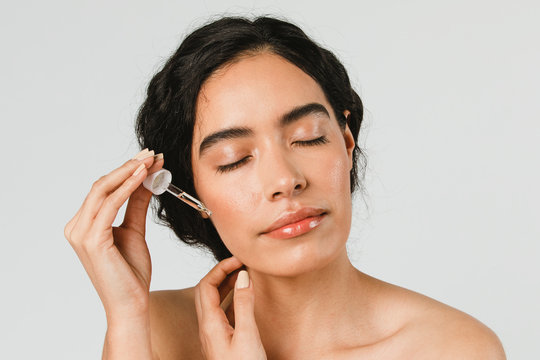 Young woman applying serum on her face