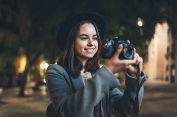 Fotomurales - Happy photographer tourist girl with retro camera take photo on background bokeh light in evening city, Blogger photoshoot photo hobby