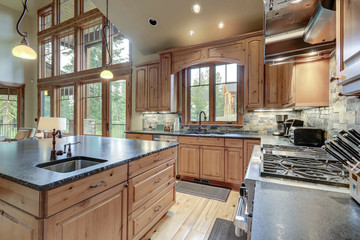 Large luxury kitchen interior with light wood hardwood floor and dark granite slab on island with...