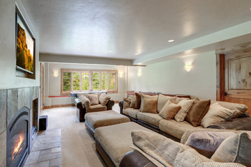 Huge bright  new luxury home family play room with soft natural wall color and light grey carpet with fireplace and soft sofa.