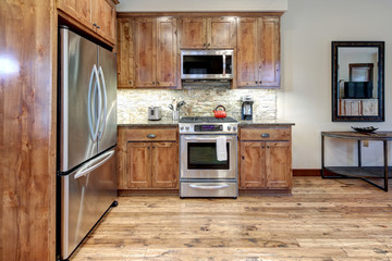 Luxury middle tone wood rich kitchen interior with grey natural stone  tiles backsplash and quarts countertop.