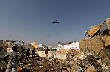 A chopper flies over the site of a passenger plane crash in a residential area near an airport in Karachi