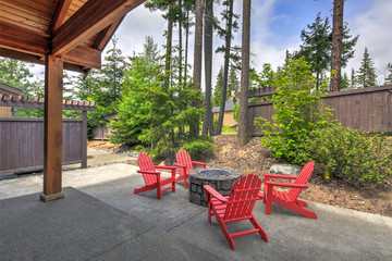 Backyard with red chairs and  fire pit.