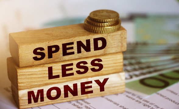 Spend Less Money on wooden block, 100 Euro currency bills and coins. Financial concept. Selective focus