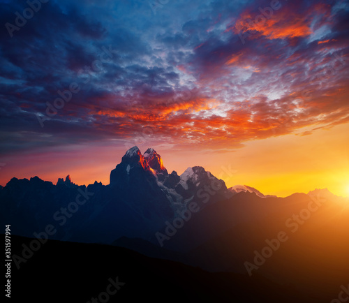 Wall mural Fantastic brilliant sunrise with rays illuminating the dark clouds. Location place of Mt. Ushba, Upper Svaneti, Georgia country.