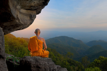 Buddhist monk in meditation Under the big stones in nature on high mountain.
