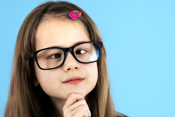 Close up portrait of a cross eyed child school girl wearing looking glasses isolated on blue background.