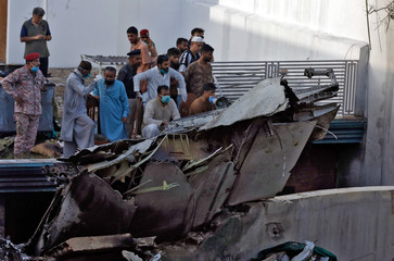 People stand next to the debris of a plane after crashed in a residential area near an airport in Karachi