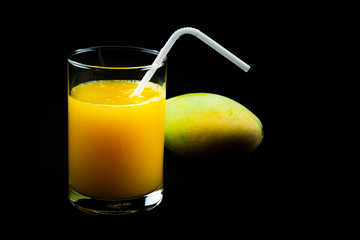 Fototapete - View of mango juice in a glass with a ripe mango on black background.