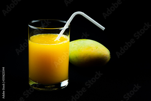 Fototapete View of mango juice in a glass with a ripe mango on black background.
