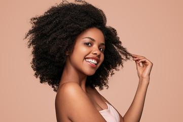 Happy black woman touching clean hair