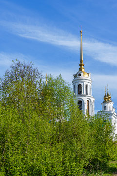 domes of an orthodox temple made of golden metal and the steeple of a bell tower against a blue sky