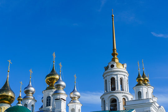 golden metal domes of an Orthodox church and the spire of a bell tower