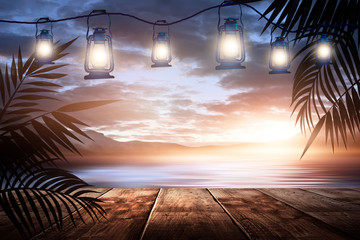 Garland of night lanterns on the pier, against the backdrop of a sea evening landscape with sunset. Palm tree branches, silhouettes, sunlight. Wooden table. Night view, open-air seascape.