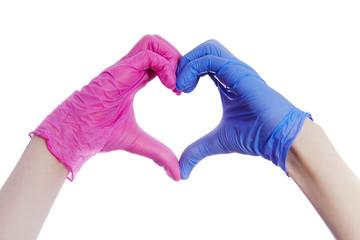Gros plan mains d'un homme et une femme formant un coeur avec  des gants bleu et rose en latex de protection médical