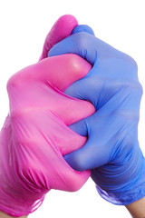 gros plan mains homme et femme mêlées portant un gant en latex bleu et rose sur fond isolé blanc