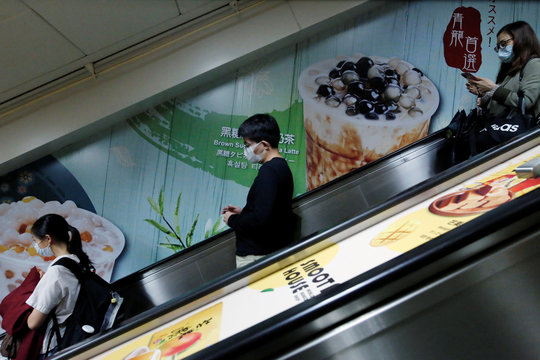 People wear face masks to protect themselves from the coronavirus disease (COVID19) while passing by posters of bubble tea drinks in Taipei,,