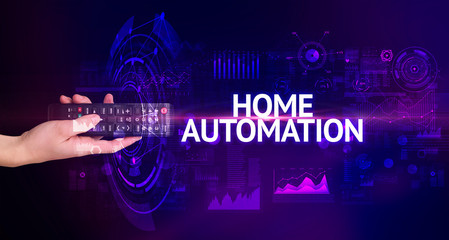 hand holding wireless peripheral with HOME AUTOMATION inscription, modern technology concept