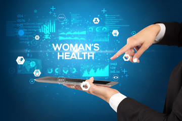 Close-up of a touchscreen with WOMAN'S HEALTH inscription, medical concept