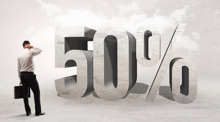 Rear view of a businessman standing in front of 50% abbreviation, attention making concept