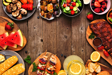 Summer BBQ or picnic food frame over a rustic wood background. Assortment of grilled meats, vegetables, fruits, salad and potatoes. Top down view with copy space.