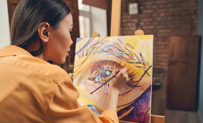 Beautiful young woman painting eye on easel at home